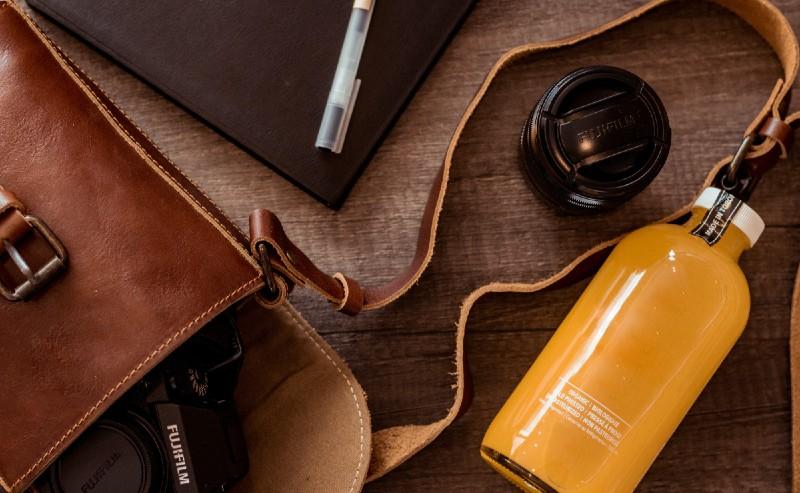 petit sac en cuir posé sur sur table ouvert avec un appareil photo à l'intérieur