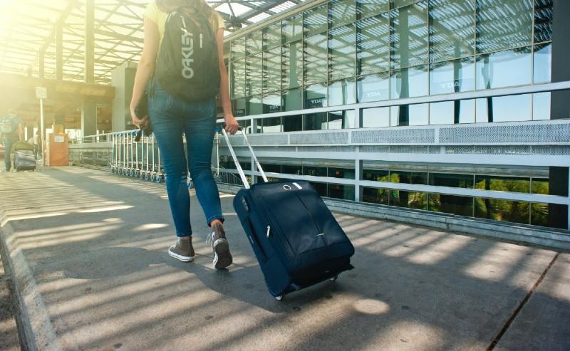 femme dans une gare routière avec un sac de voyage à roulette