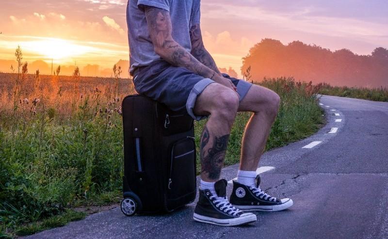 un homme assis sur son sac de voyage