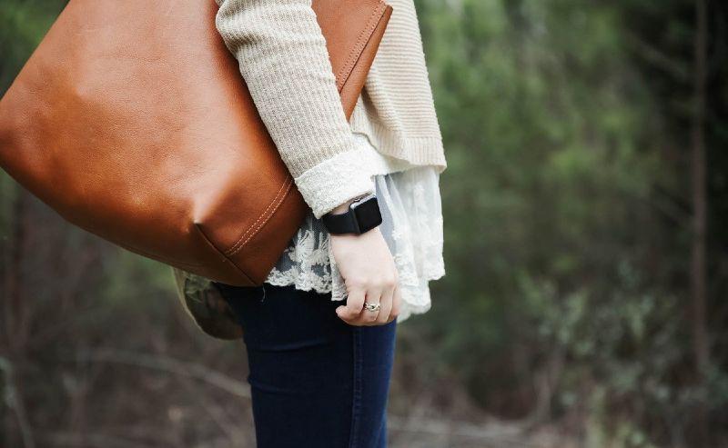 femme qui porte un sac en cuir marron à lépaule