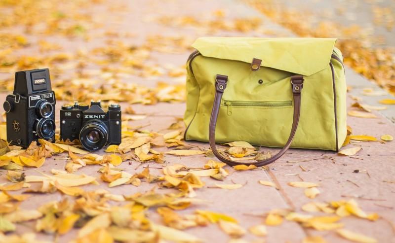 sac de voyage femme posé au sol avec des appareil photos à côté