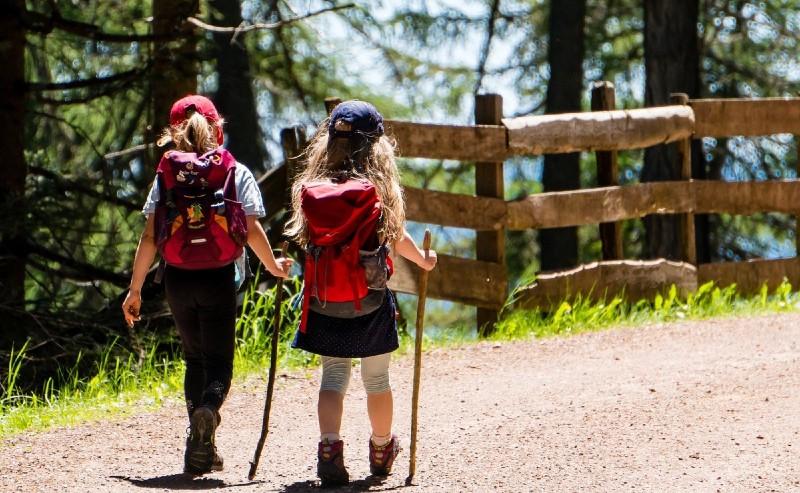 deux petites filles avec des sac de voyage sur le dos qui marche sur un chemin de campagne